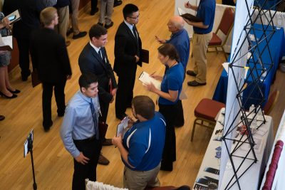 Three males talk with recruiters at a job fair.