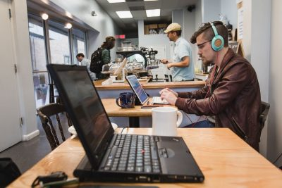 Virginia Tech male student studying with headphones on in a coffee shop.