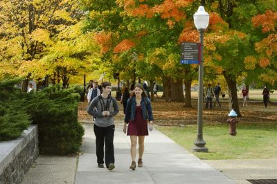 Students walking down a sidewalk on campus in the autumn.