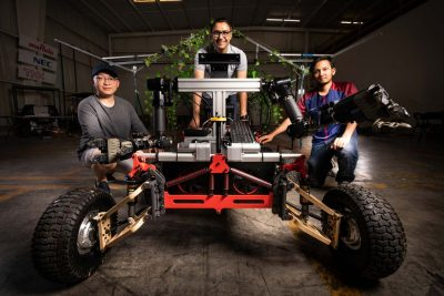 Graduate students pose by their grape harvesting robot in a warehouse.