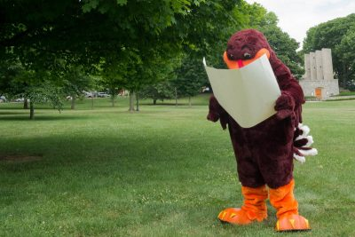 Hokie Bird looking at a map on the Drill Field.