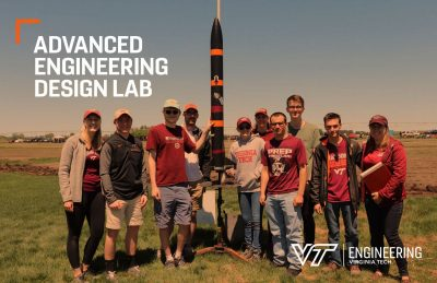 Rocketry team with rocket in a field.