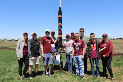 The invents rocketry team poses for a group photo with a rocket outside.