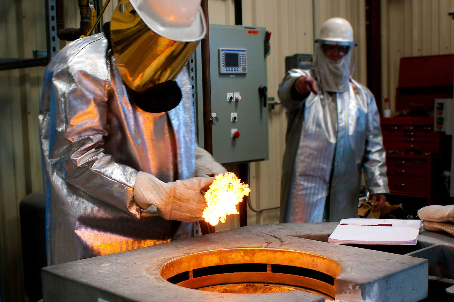 A Material Science student works with molten material in a lab and is wearing a fire suit.
