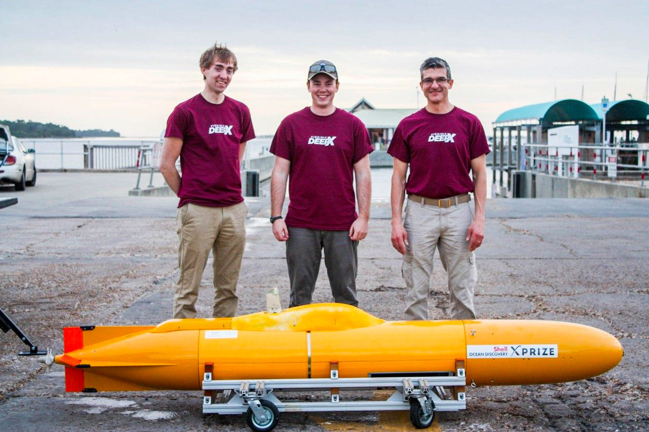 Members of the DeepX team pose outside in front of their submarine.