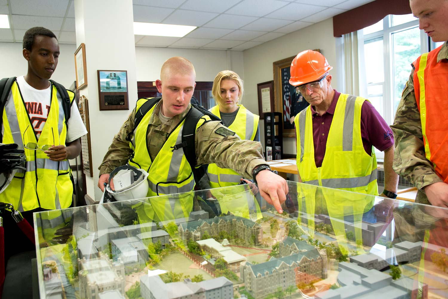 Meyer's-Lawson students look over a table with a 3D model of the new Virginia Tech Cadet dorms.