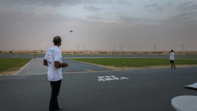 Graduate student flying a drone outside in the desert in Abu Dhabi.