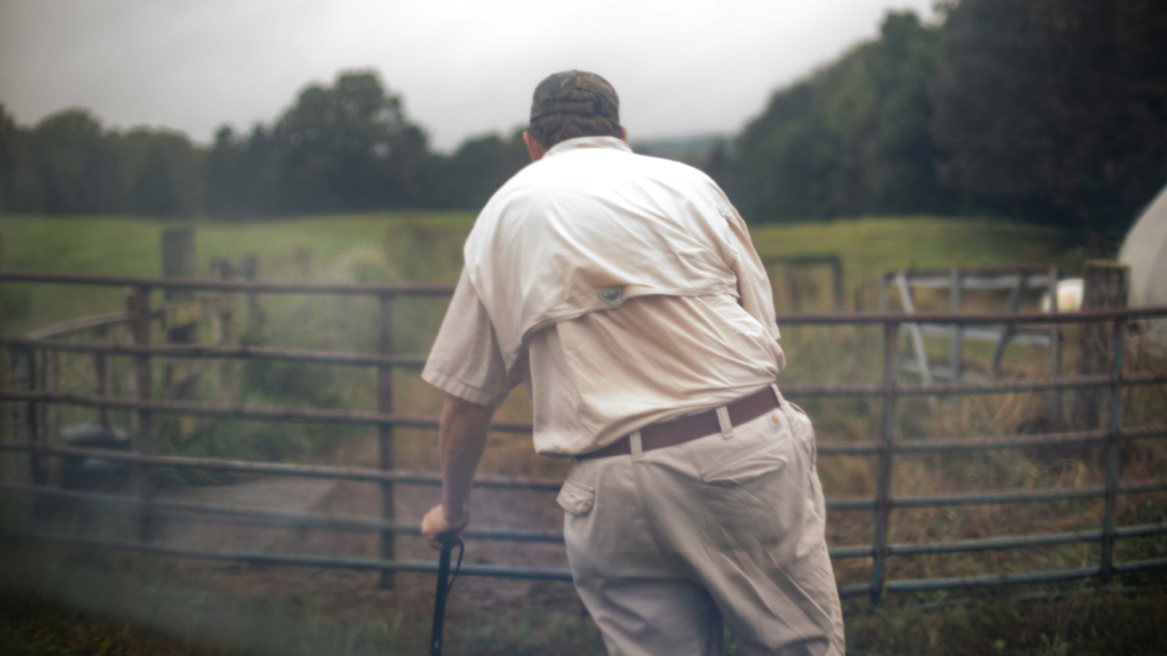 An old farmer uses his cane to walk around his farm.