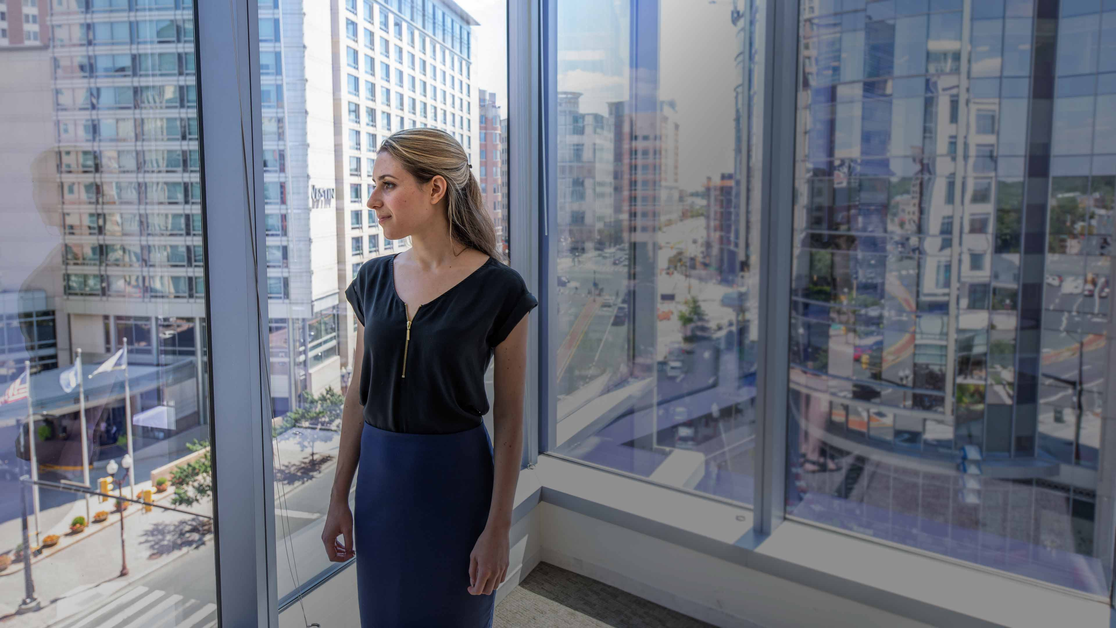 A woman stands in front of a window. Behind her stand tall buildings with large glass windows in a modern cityscape.