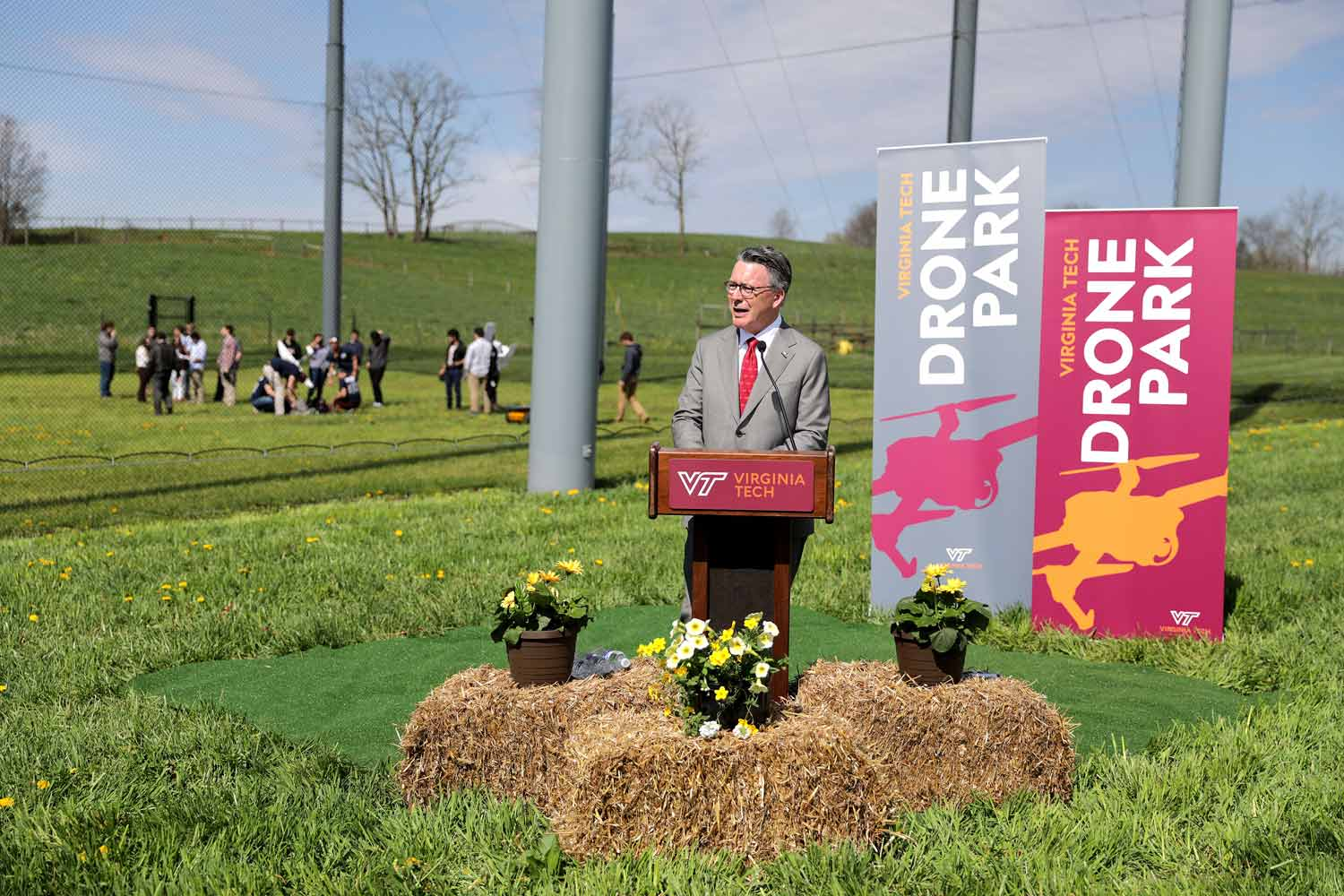 President Sands speaks at the opening ceremony for the drone park at a lectern in front of the netted park walls.