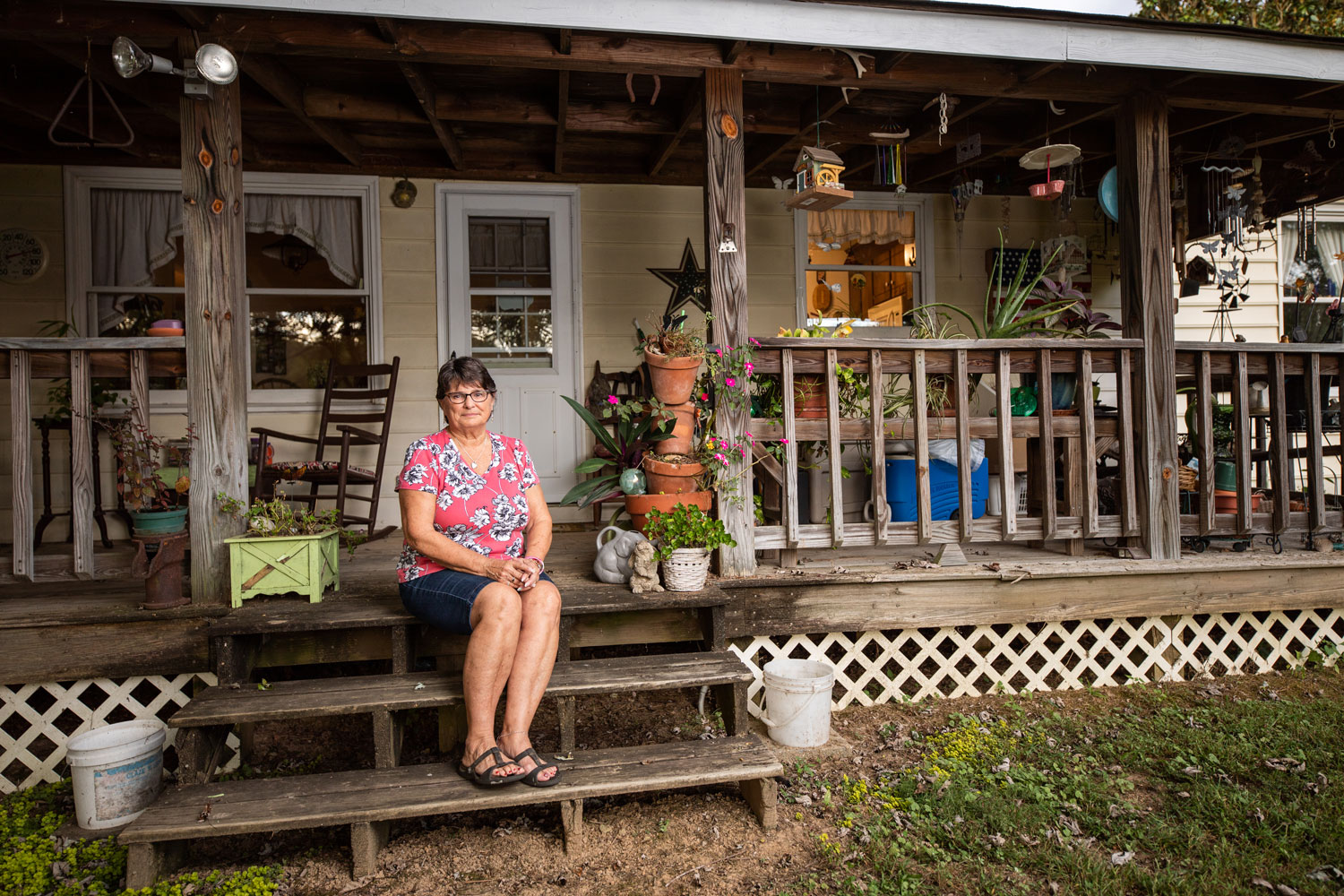 A woman sits on a porch filled with plans and wind chimes outside a house.