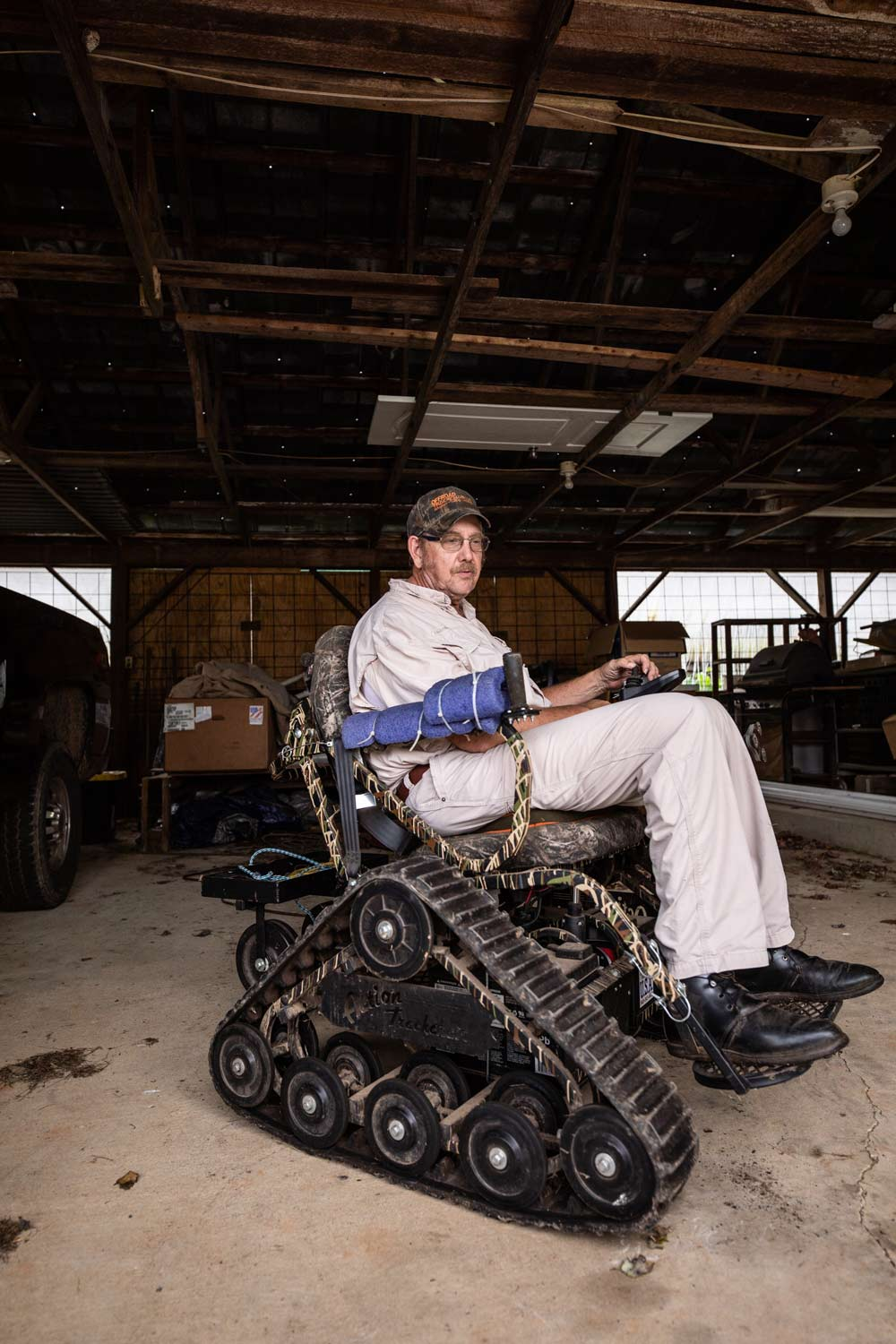 A man sits in a wheelchair that's fitted with a sturdy belt around the wheels that helps navigate rough terrain.