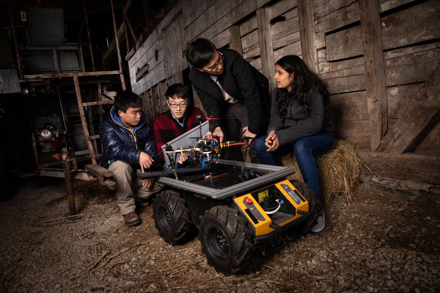 Four students crowd around a drone and ground vehicle while sitting inside a barn.
