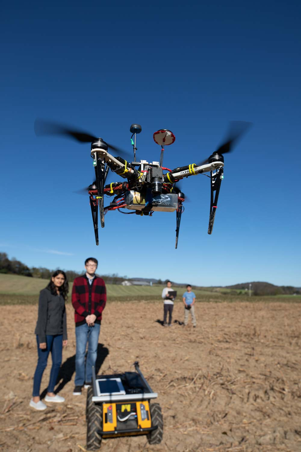 A drone hovers in the center of the phone. In the background students stand near a ground vehicle while the drone operators stand further back.