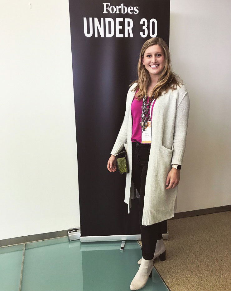 Paige Kassalen in front of a Forbes Under 30 display banner.