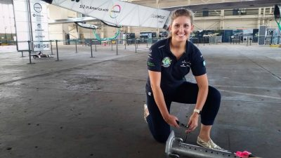 Paige Kassalen posing in a hanger in front of the Google Solar Impulse plane.
