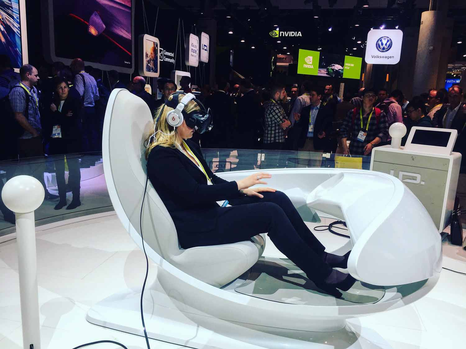 Paige Kassalen in a simulator at a tech trade show with goggles and headphones on.
