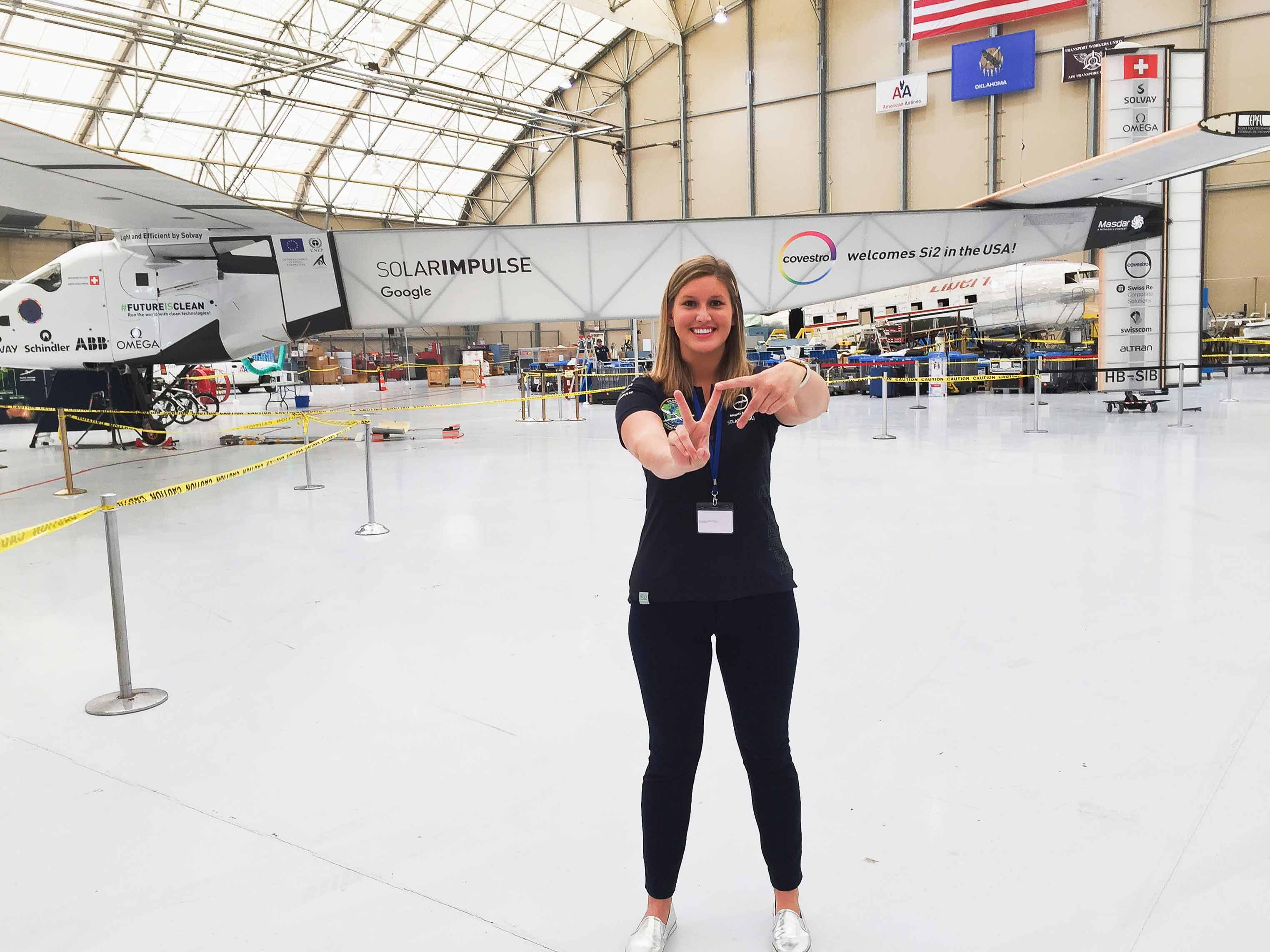 Paige Kassalen making the VT hand sign with her fingers in a hanger in front of the Google Solar Impulse plane.