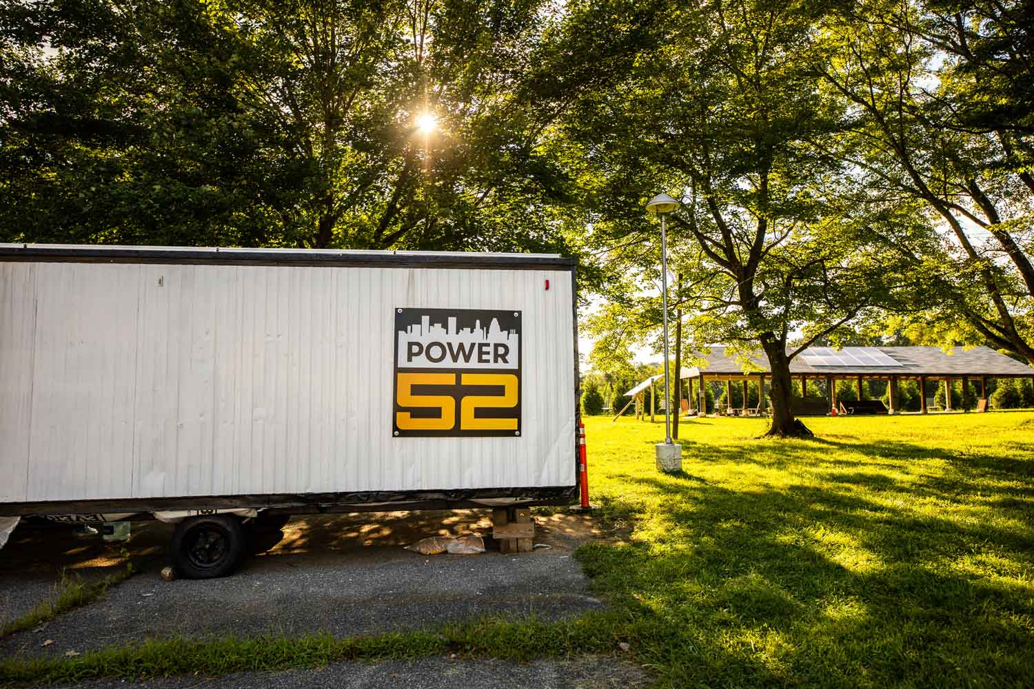 "A trailer sits in a grassy area with a sign on it that reads in bold yellow font ""Power52."""