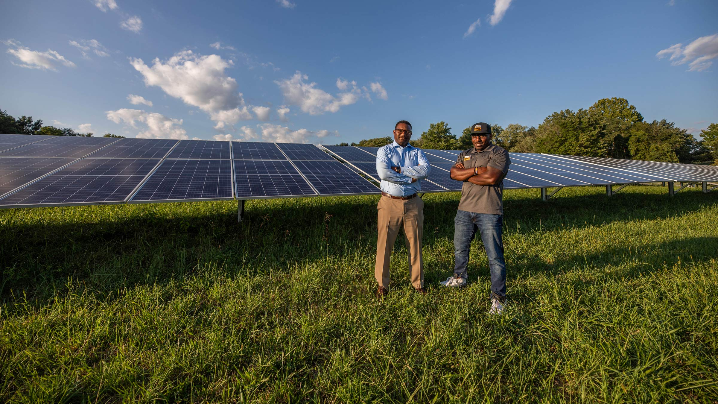 Two men pose in front of solar panels in a field.