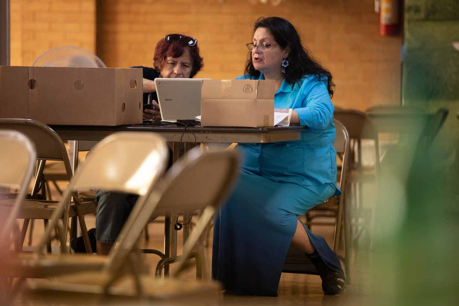 Delia Barajas works on a laptop in a church basement with a volunteer.