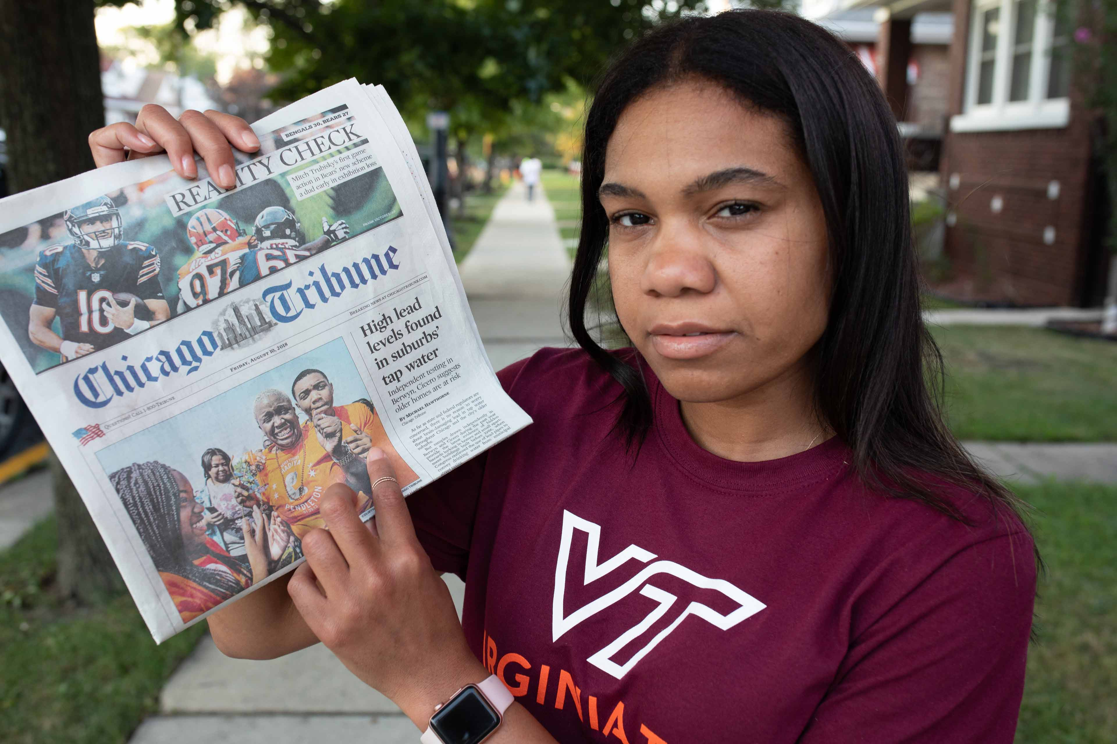 Chivonne Battle holding the Chicago Tribune with the water story on the cover.