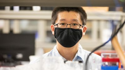 Ling Li with a mask on in his lab.