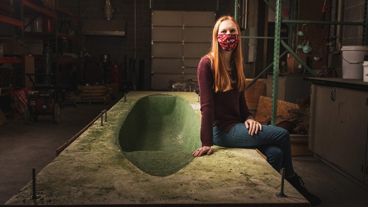 Jessica Viehman poses with the mold for the concrete canoe.