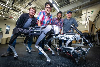 Virginia Tech professor poses behind two dog-like robots with three of his graduate students.
