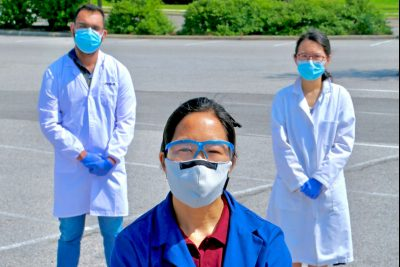 Linsey Marr and two others pose with masks in a parking lot.