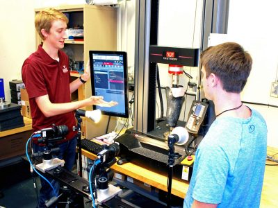 Two graduate students are testing a carbon fiber prosthetic under load in a lab.