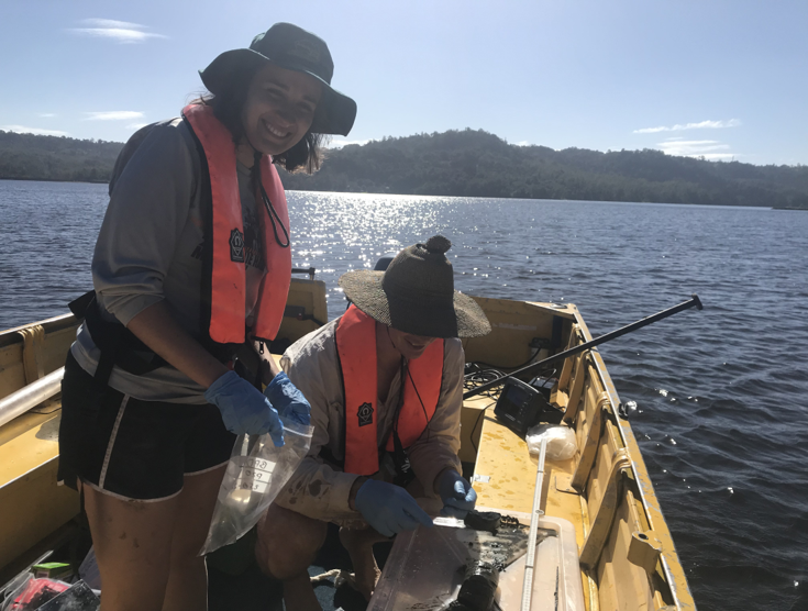 students taking water samples from boat