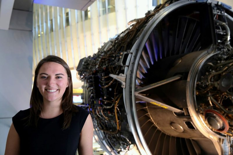 Grad student standing by an airplane engine inside of Goodwin Hall.