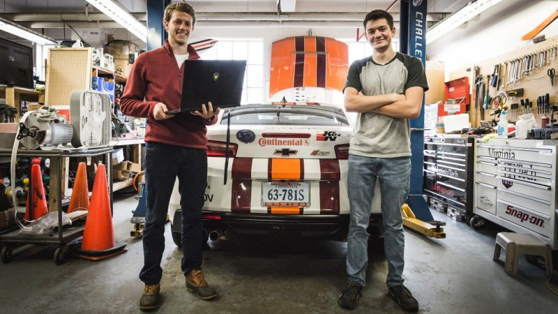 Two students standing in front of a car in the ware lab