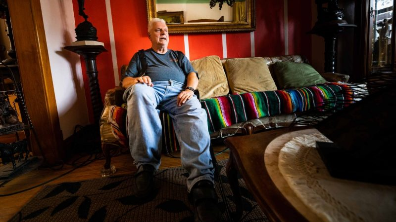 An elderly Cicero IL resident sits on the couch his colorful living room.