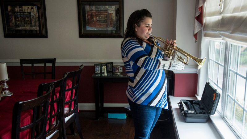 Josie Fraticelli, a young, 12-year-old girl, stands in front of a window in her home, playing a trumpet using a white prosthetic hand.