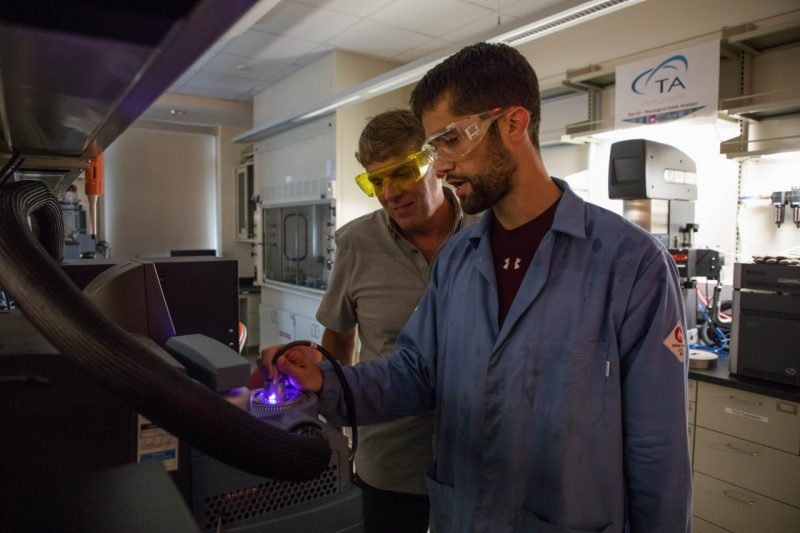 Two researchers work with a glowing purple device in a darkened lab.