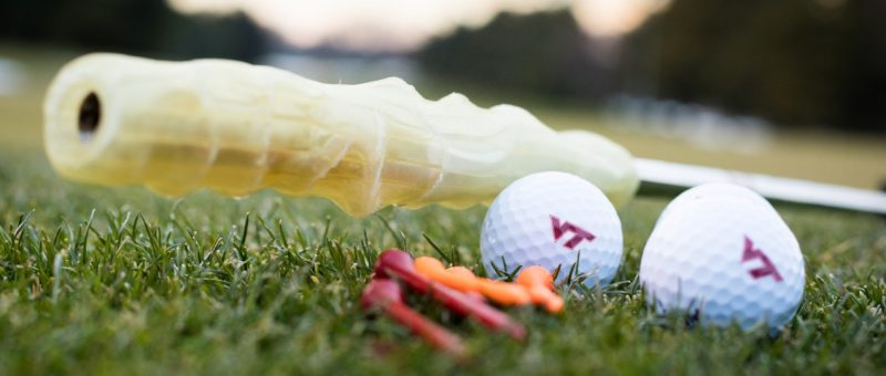 3D printed custom golf grip on a golf course with VT golf balls and tees