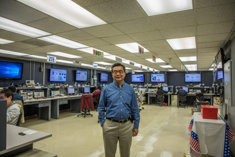 Fred Lee stands proudly in the middle of an electronics lab while students work at stations around him.
