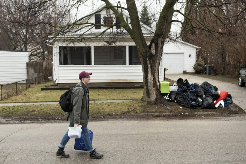 A student carries testing kits to homes in a neighborhood. In the background, one household has thrown out furniture on the roadside curb.