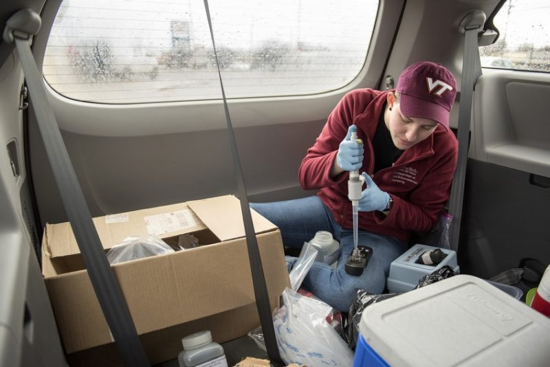 A Virginia Tech student tests water samples, sitting in the cargo space of a mini-van