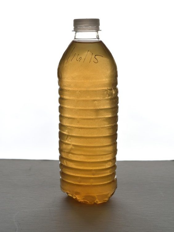 A photo of a water bottle with a date written on it. Inside, the water is brown.