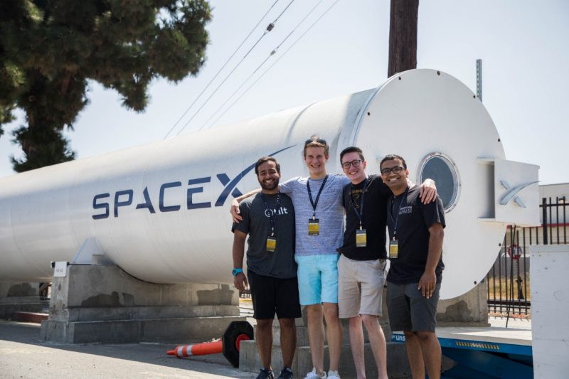 Proud Virginia Tech Hyperloop team members pose arm in arm in front of the Hyperloop track at SpaceX.