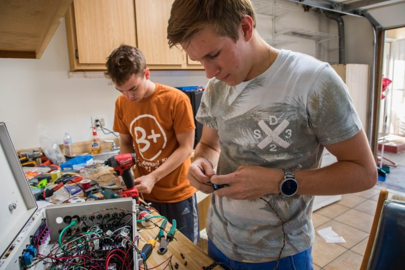 Two Virginia Tech work on electrical components at a workbench.