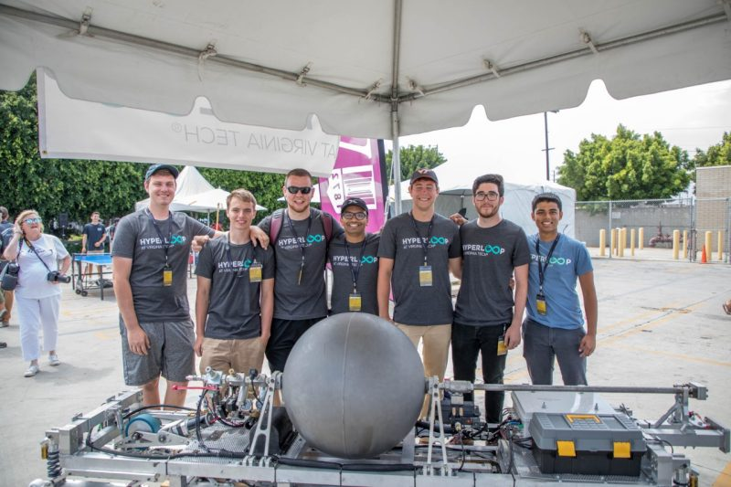 Seven Hyperloop team members pose for a group shot in front of their Hyperloop pod.