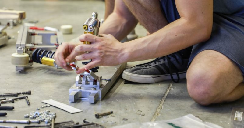 A student works with his hands and some tools in this close up shot.