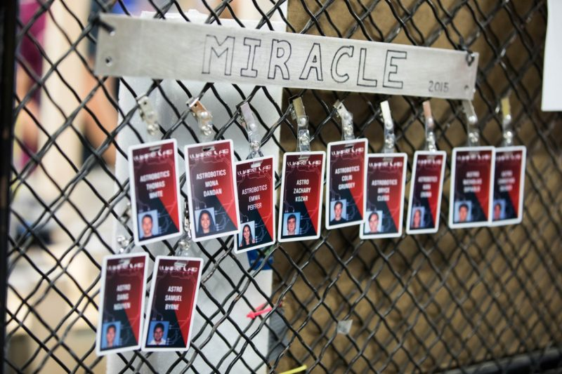 "Badges hang from a chain link fence inside the Ware Lab. Above them hangs a sign that says, ""Miracle."""