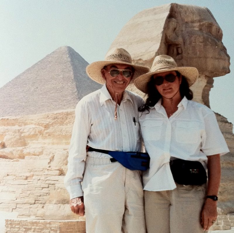 Joe and Jenna, both in white shirts and khaki pants, pose in front of pyramids in Egypt.