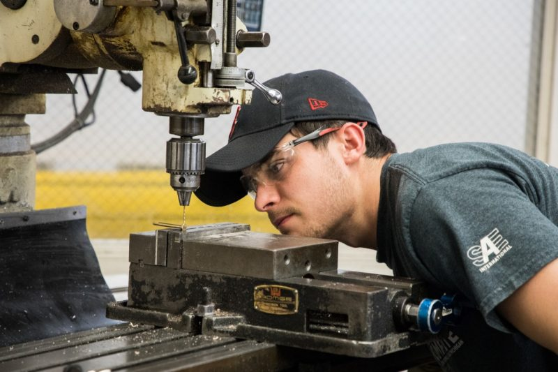 A student focuses on the alignment of a bit in a drill press in the machine shop.