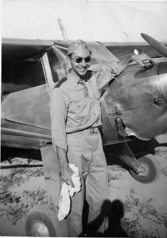 A black and white photo of Joe, posing in front of a plane.